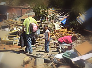 Child looking through earthquake rubble with parents