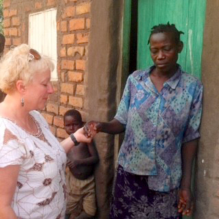 Fran Hallgren praying with African woman